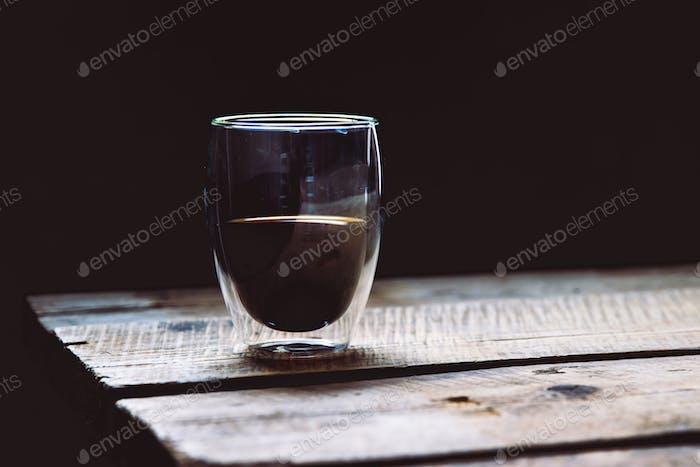 Transparente Tasse Espresso auf einem Holztisch
