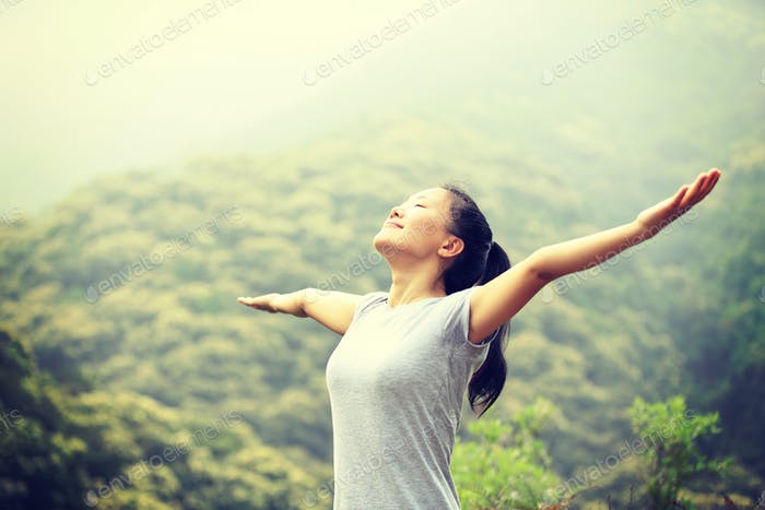Young asian woman breathing fresh air in spring nature
