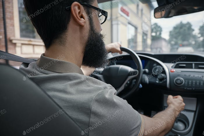 Handsome man driving the car side view