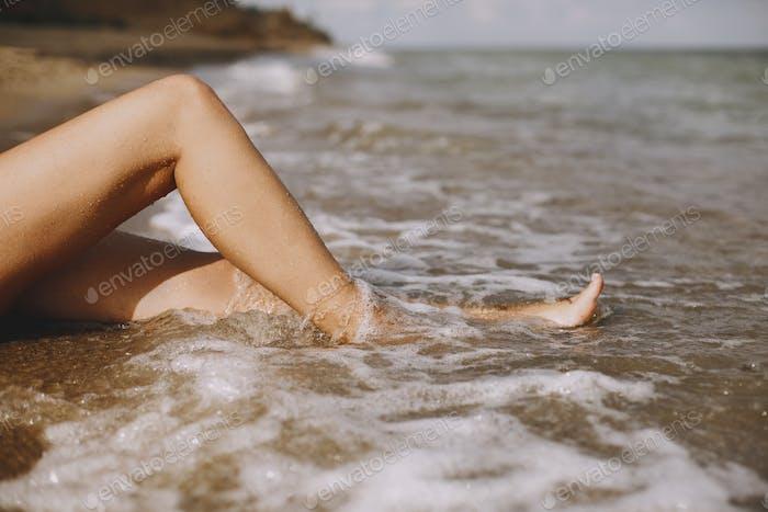 Legs in waves foam on beach closeup