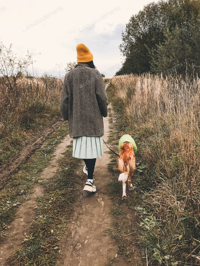 Hipster girl in yellow hat and in coat walking with her golden dog in coat