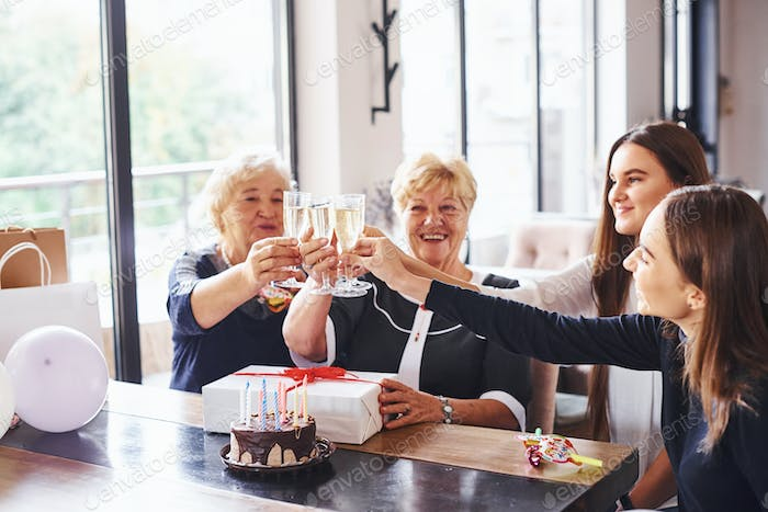 Knocking glasses. Senior woman with family and friends celebrating a birthday indoors