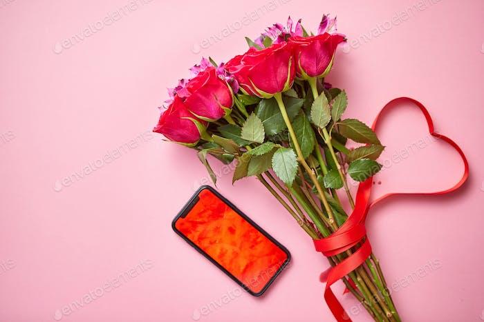 Rosa Rosen Blumenstrauß mit hart geformter Schleife und Handy mit Kopierraum Bildschirm