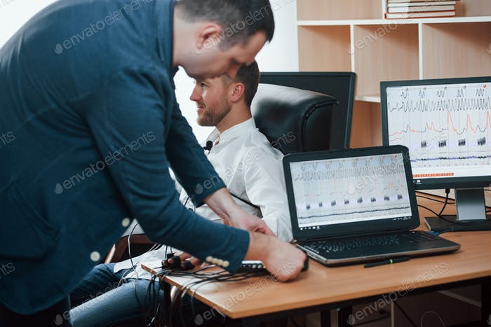 Connects cables. Preparation for the polygraph test. Conception of the lie detector