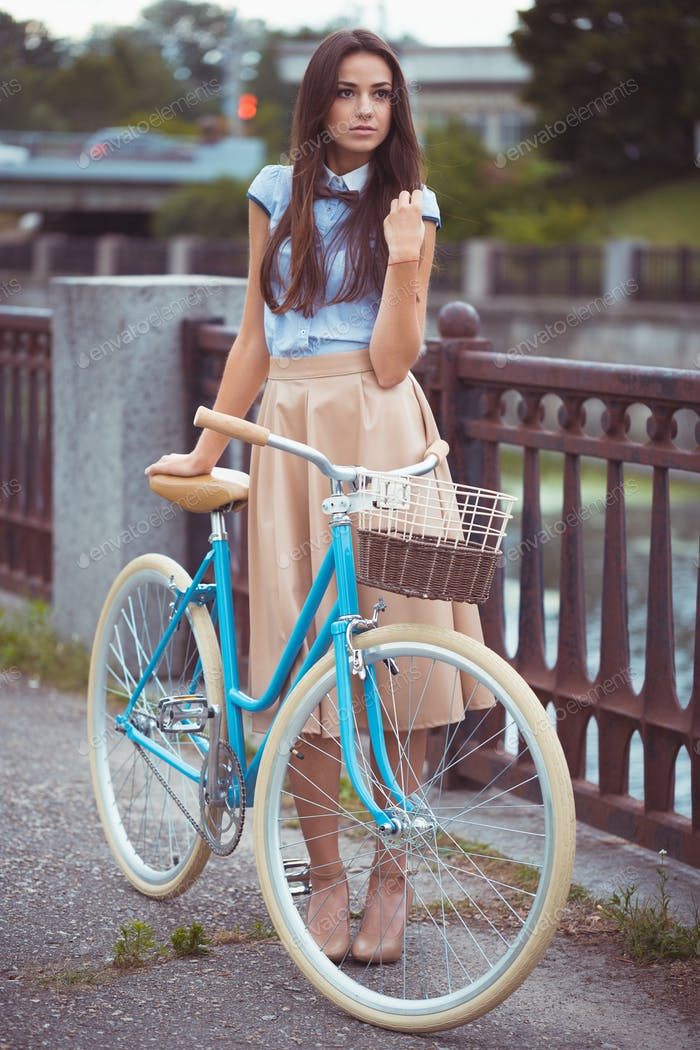 Thumbnail for Young beautiful, elegantly dressed woman with bicycle