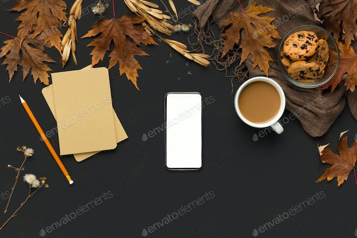 Cellphone with blank screen on cozy autumn background