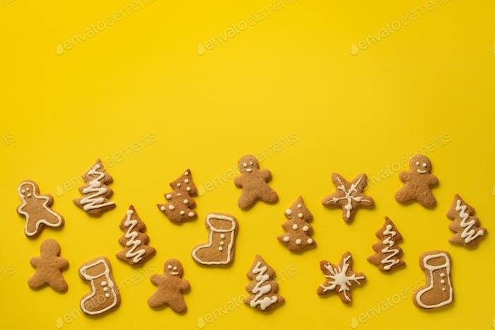 Weihnachten handgemachte Kekse auf gelbem Hintergrund mit Kopierraum. Muster von Lebkuchenmännern