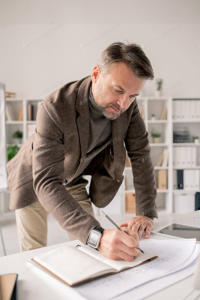 Mature architect bending over open notebook on desk while making working notes