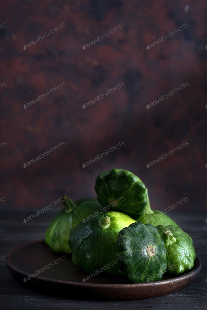small size patty pan patisson squash on plate on dark wooden background with copy space