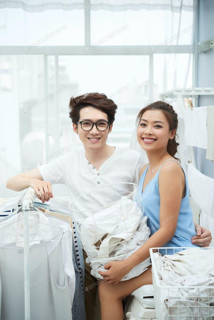 Cheerful couple doing laundri