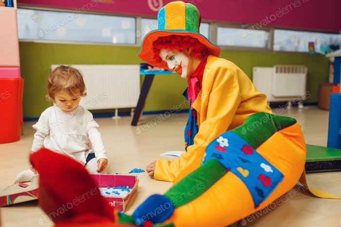 Funny clown play with joyful little girl together