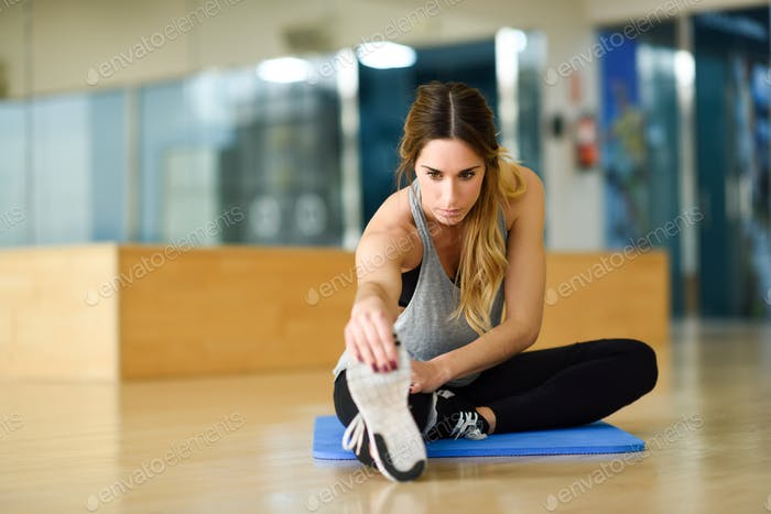 Young woman stretching their legs in gym.