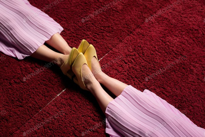 partial view of female legs in yellow shoes reflecting in mirror