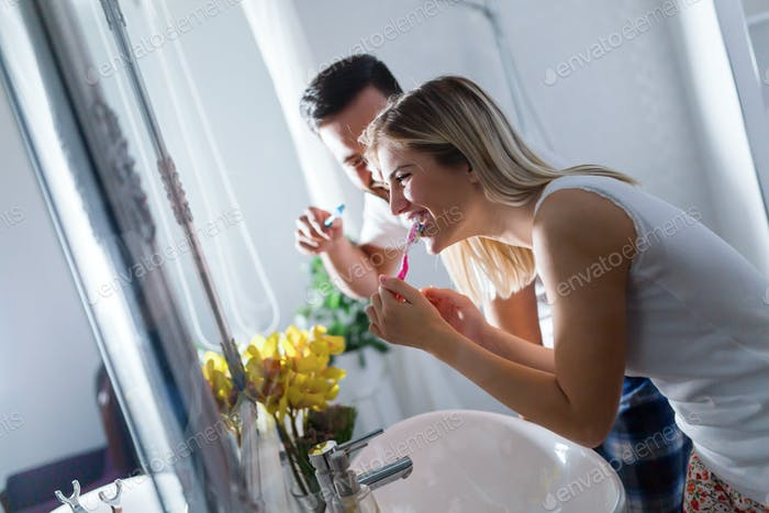 Attractive couple brushing teeth in morning together
