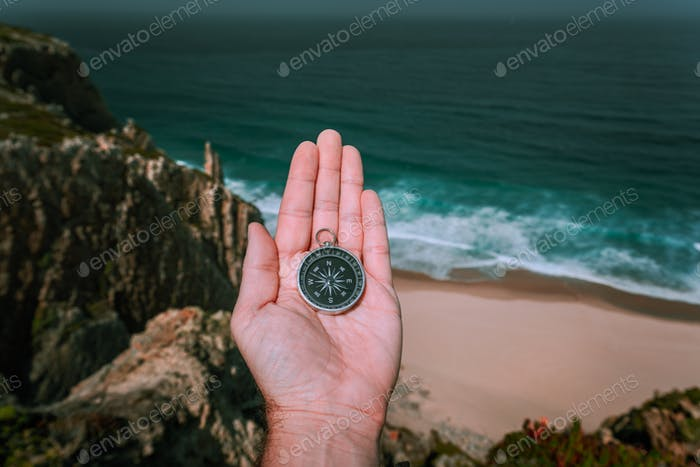 Looking at the compass in man hand palm symbolling adventure-seeking concept against sea and waves