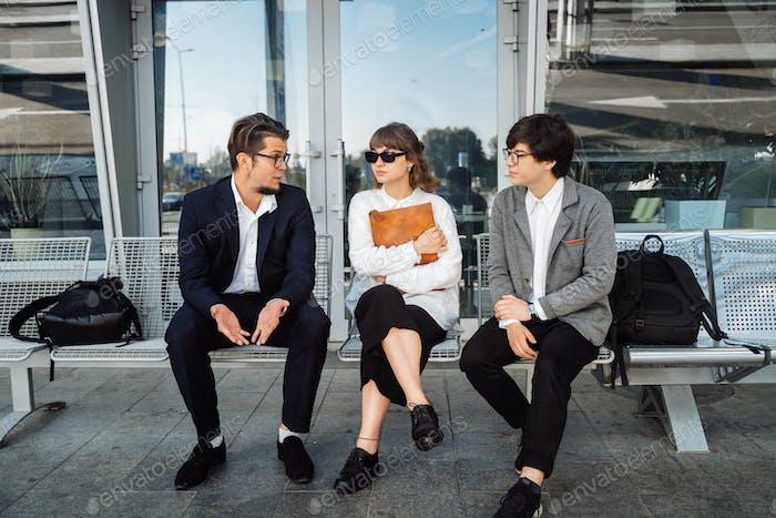 Zwei Geschäftsleute und eine Sekretärin diskutieren ein wichtiges Thema außerhalb