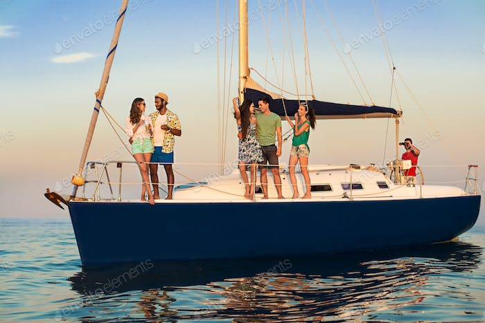 Young people standing on yacht.