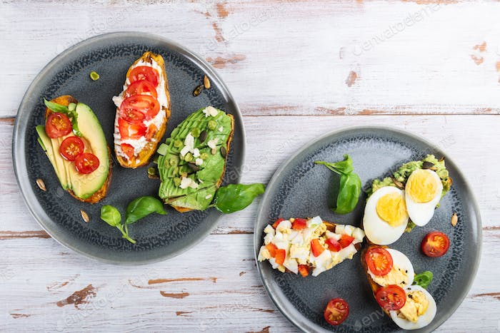 Sweet potato toasts with avocado, eggs, tomatoes and sesame seeds