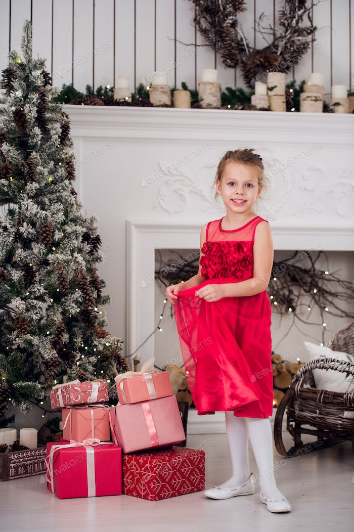 Little beautiful girl in red evening dress the Christmas tree.