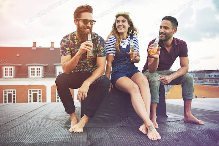 Happy group of three barefoot adults drinking beer