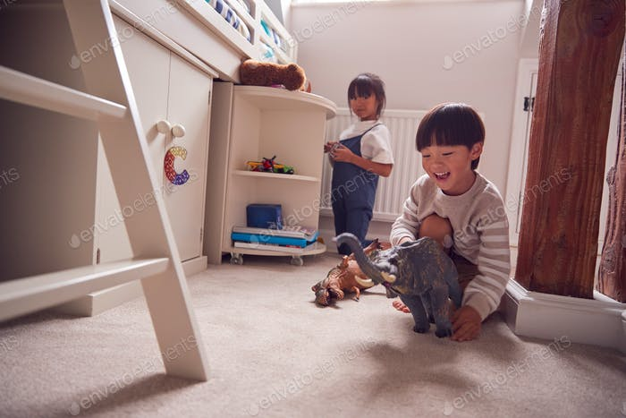 Asian Children Having Fun Playing With Toys In Bedroom Together