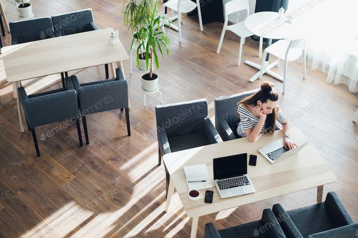 Junge Frau, die beiläufig auf ihrem Laptop in einem Café arbeitet. gelangweilt attraktiv weiblich sitzend mit einer Tasse