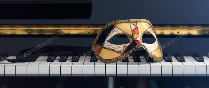 Carnival mask on piano keyboard, front view