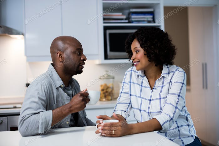Couple interacting with each other while having coffee in kitchen