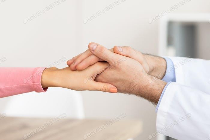 Nahaufnahme eines männlichen Arztes, der die Hände einer Patientin hält