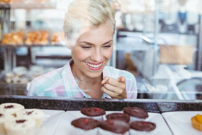Pretty woman pointing a cup cake at the bakery
