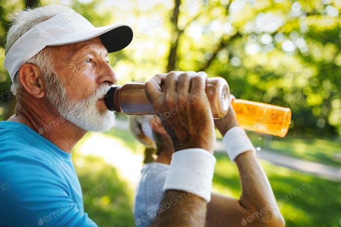Feuchtigkeitsspendend. Sportliche Seniorin Trinkwasser im Park