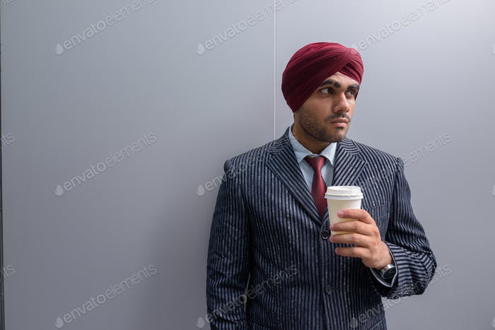Indian businessman outdoors in city holding coffee cup while thinking