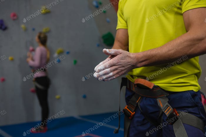 Midsection of male athlete applying chalk powder to hands in club
