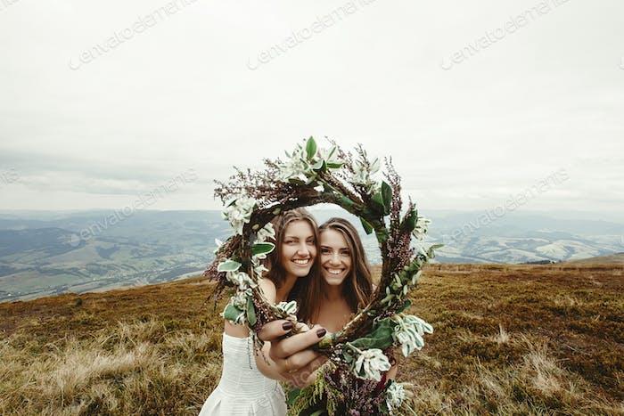 stilvolle Brautjungfer und wunderschöne Braut lachen und Blick durch Kranz