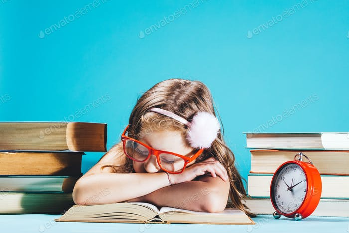 Little girl sleeping on an open book in funny red glasses
