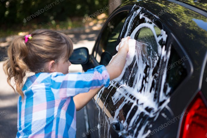 Teenage girl washing a car
