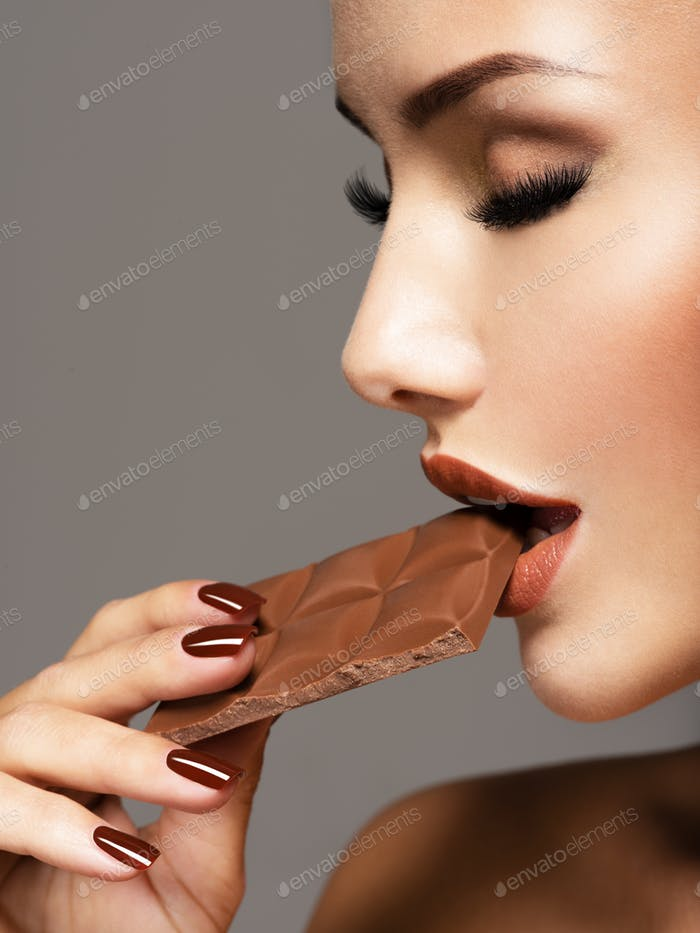 Glamour beautiful woman eats  chocolate with delight