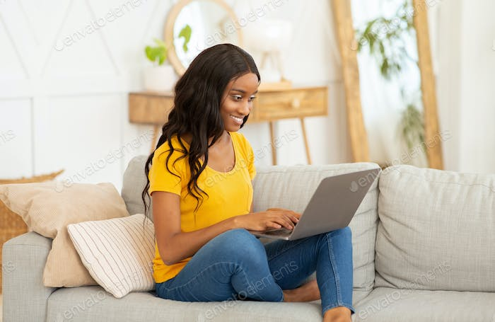 Gorgeous black lady studying or working online from home, using laptop computer