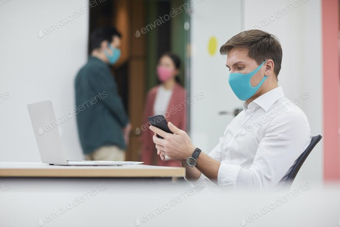 Businessman using phone at office