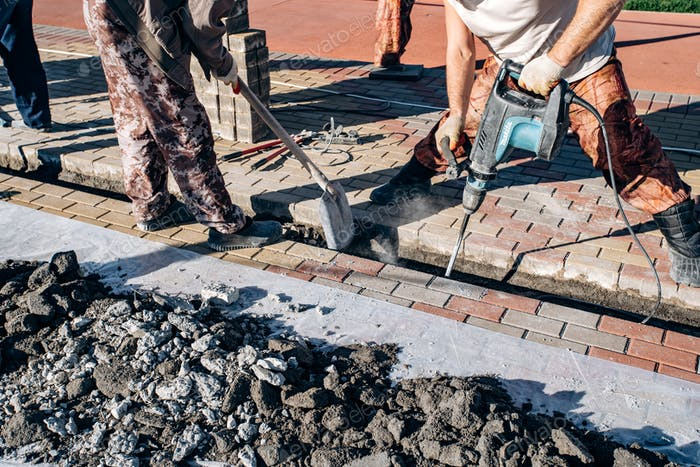 Workers laid paving slabs. Two workers lay paving slabs.