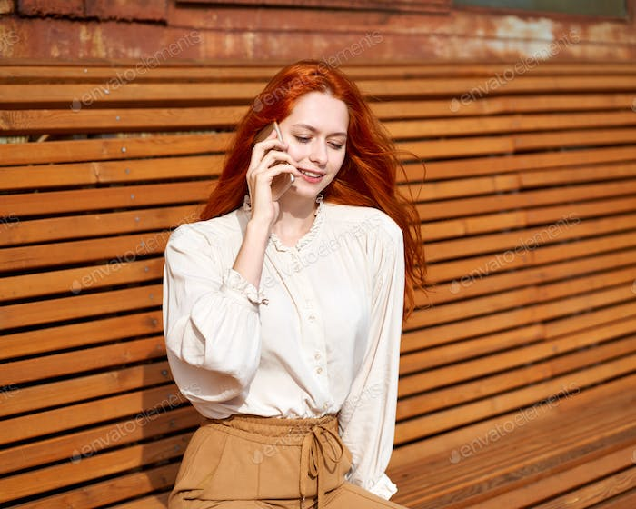 Red-haired woman talking on cell phone. Beautiful stylish fashion model