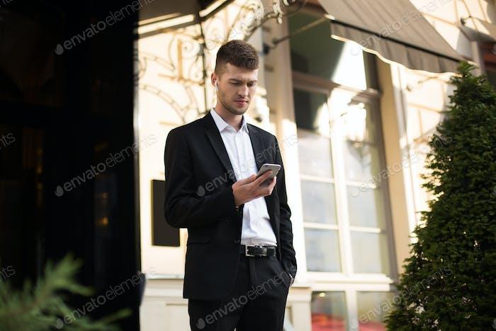 Молодой вдумчивый бизнесмен в черном костюме и рубашке с проволокой