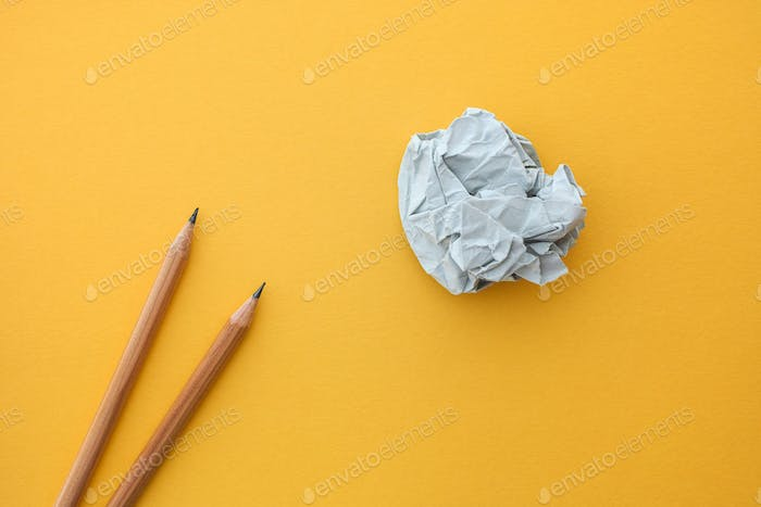 Two pencils and paper ball