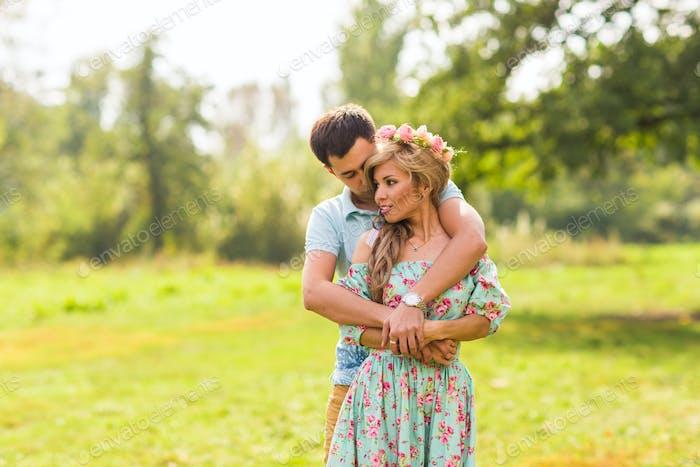 Ein Paar in der Liebe schöne junge Männer umarmt in einem Sommerpark an einem sonnigen Tag