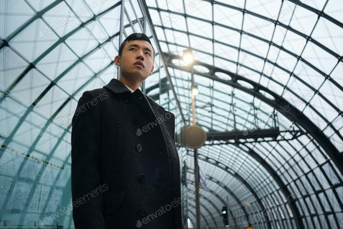 Young stylish Asian businessman in coat confidently waiting train at subway station