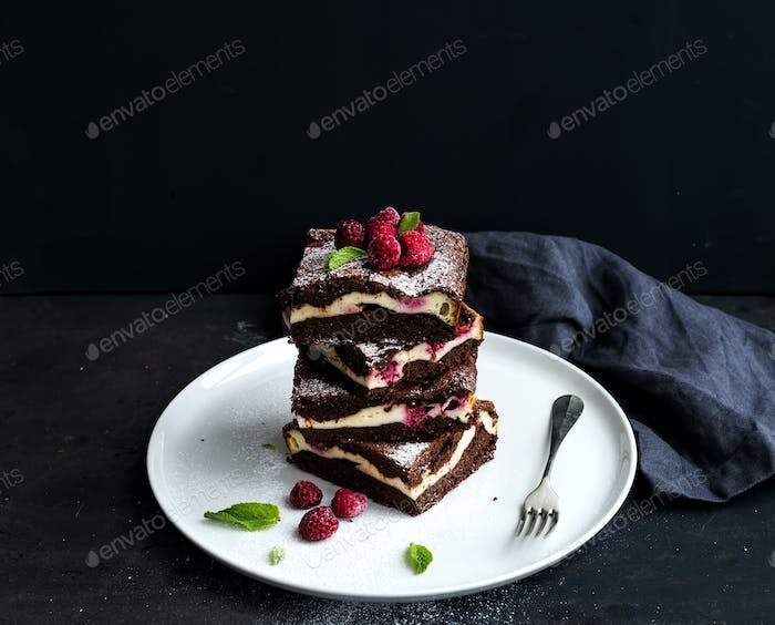 Brownie-cheesecake tower with raspberries on white plate, black backdrop, copy space.
