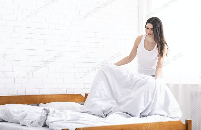 Young woman making bed alone in morning