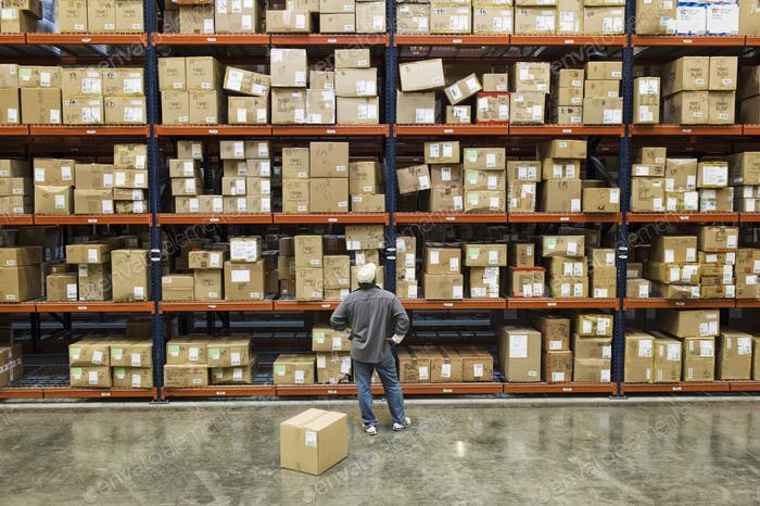 Warehouse worker checking inventory next to large racks of cardboard boxes holding product in a