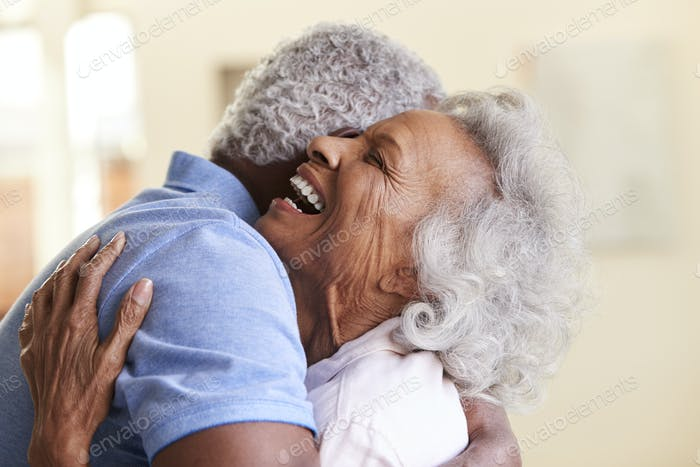 Profile Shot Loving Senior Couple Hugging At Home Together