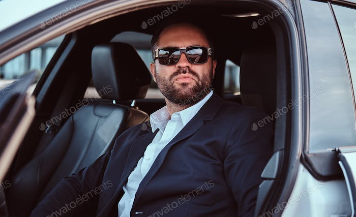 Businessman in sunglasses dressed in a formal suit sitting on the front seats in the luxury car.